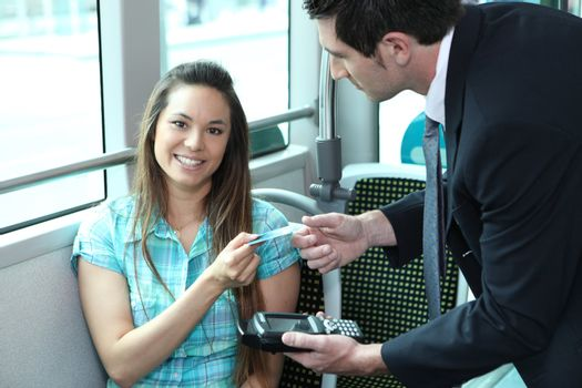 A young female passenger showing her card to a controller on a bus or a tramway.