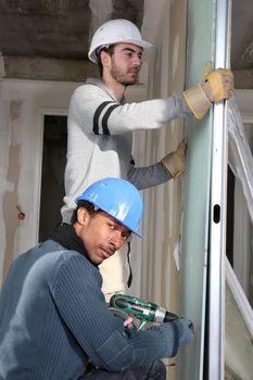 Tradesmen installing drywall