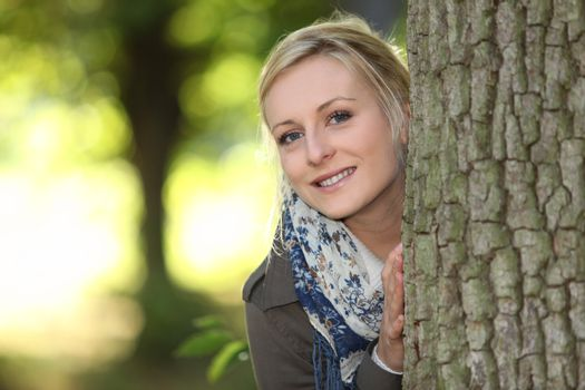 portrait of adorable young blonde outdoors with hands resting on bole