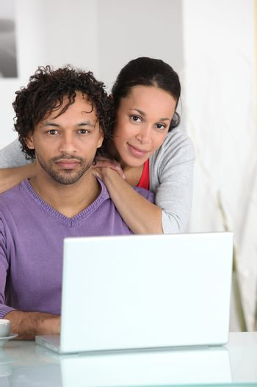 Mixed-race couple at laptop