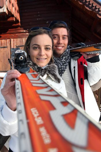 Couple stood by chalet with skis