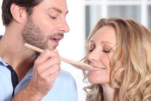 man having her wife taste preparation