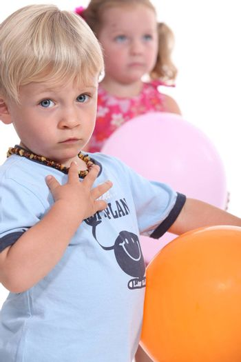 Young boy wearing an amber teething necklace and his friend playing with balloons