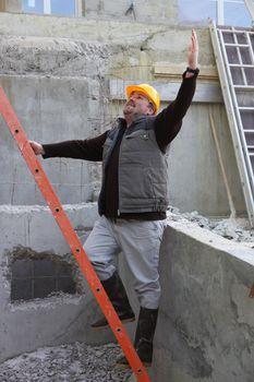 Builder stood by ladder waving