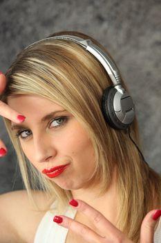 Woman wearing headphones making youthful gesture