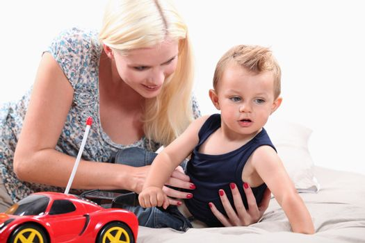 Young mother with her son and a remote controlled car