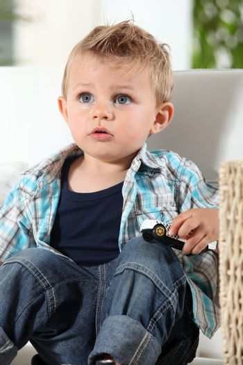 Little boy watching television with a toy car