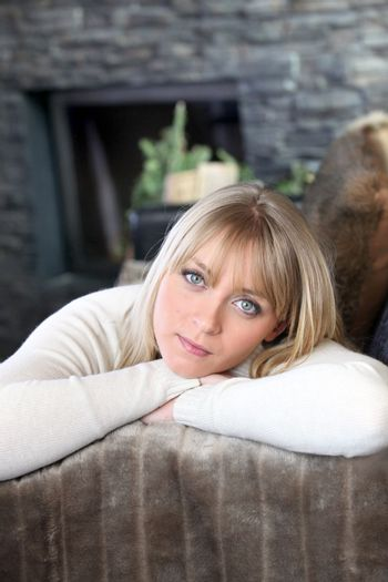 portrait of good-looking young blonde in chalet with face resting in arms