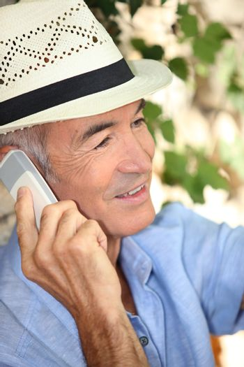 Man wearing a straw hat and talking on his mobile phone