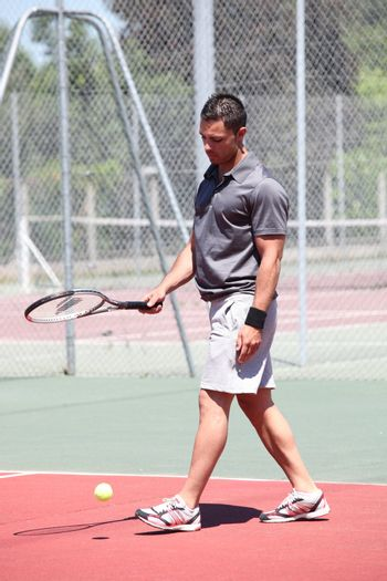 Man stood on outdoor tennis court bouncing ball with racket