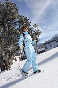 full-length shot of female skier walking in snow