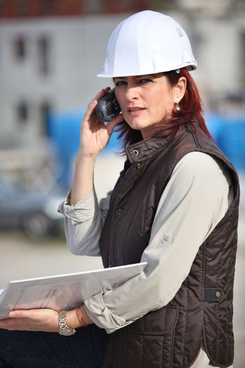Female site manager using radio to communicate