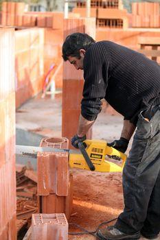 Mason sawing bricks