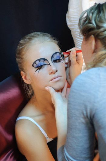 Model preparation by the visagiste before a photoshoot.