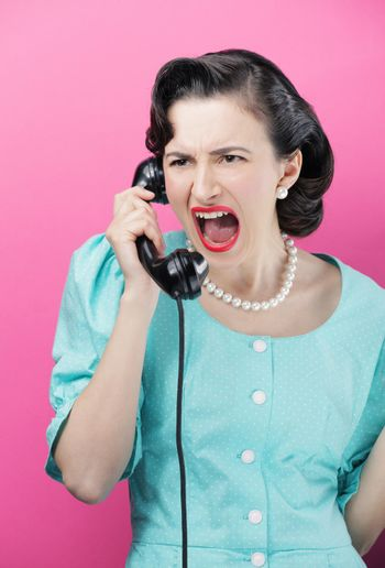 Woman yelling into an old-fashioned telephone
