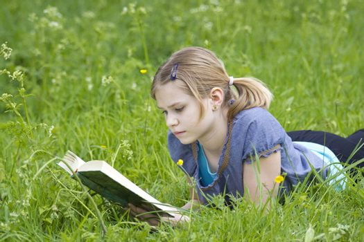 A little girl reading a book outdoor, warm spring day