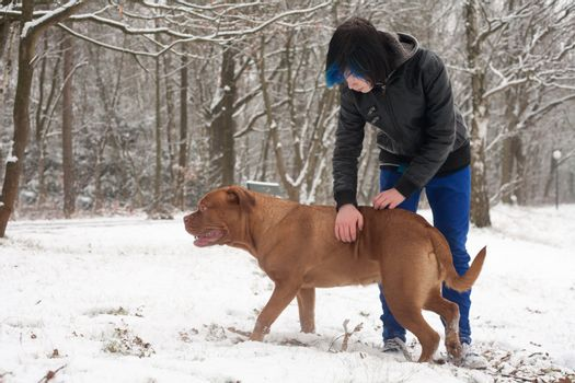 Funky boy is having fun with his dog in the snow