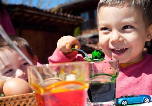 Two sweet kids dyeing eggs for easter, focus on boy holding quail egg with spoon