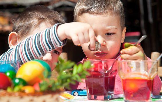 Two sweet little boys colouring quail easter egg