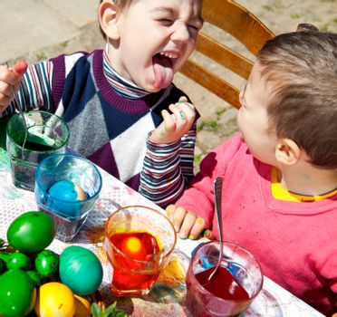 Two sweet little boys painting Eatser eggs playing