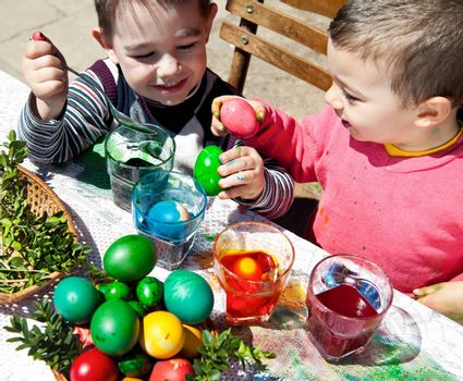 Two sweet little boys having fun dyeing eggs for easter