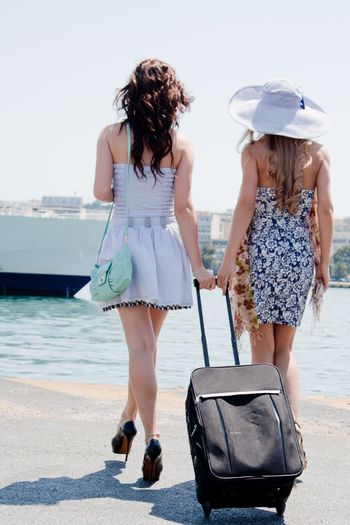 Portrait of two young and beautiful girls in the background of a large ocean liner