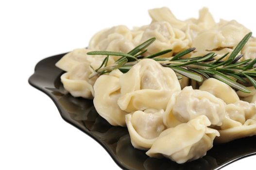 Ready to eat ravioli on a plate. Decorated with rosemary. Isolated on white.