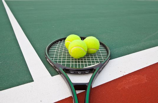 Tennis court with balls and racket