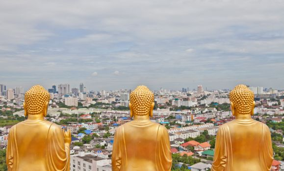 Buddha statue from behind look over the city of Bangkok