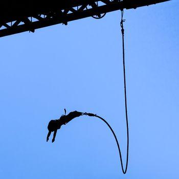 Bungee jumper against blue sky