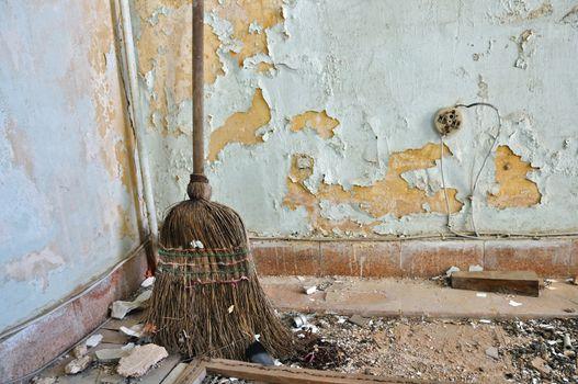 straw broom on filthy floor