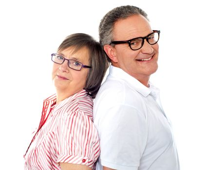 Portrait of smiling aged couple posing back to back