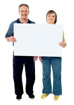 Happy senior couple holding a white placard