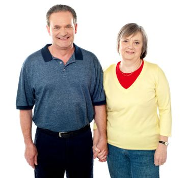 Loving senior couple posing with hand in hand
