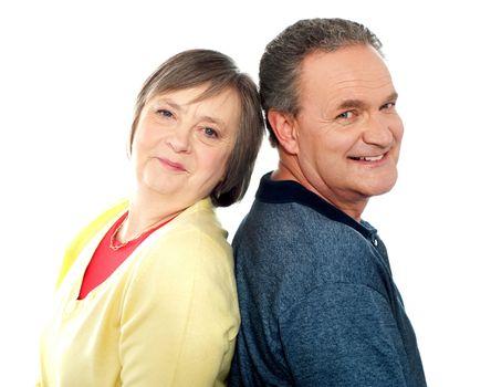Portrait of senior couple back to back in studio