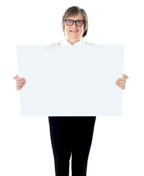 Senior businesswoman posing with blank placard