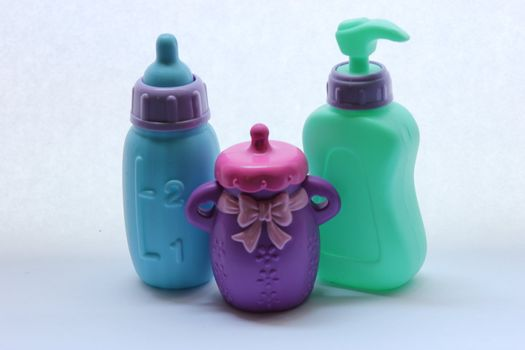 Toddler toys that include two bottles and a soap dispenser.