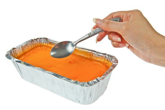 Butter cake topping with jelly orange and a hand with spoon