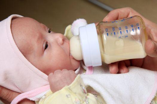 The little girl eats porridge from a bottle