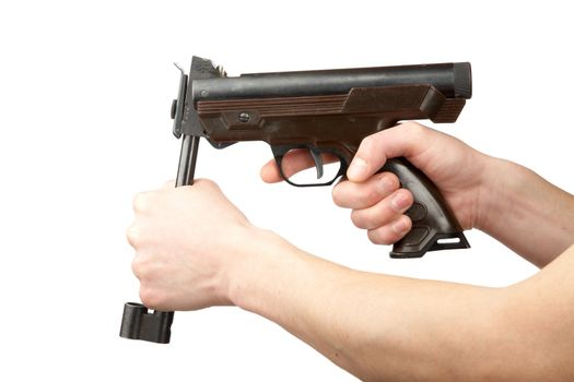 Man's hands charge a pneumatic pistol