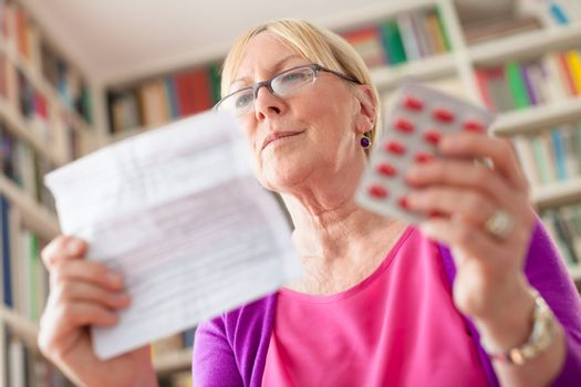 Senior woman with medication pills and prescription
