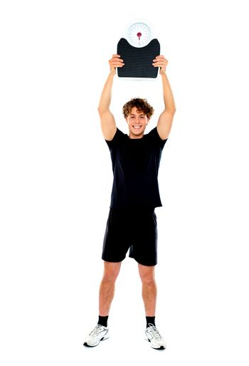Male athlete holding weighing machine over his head
