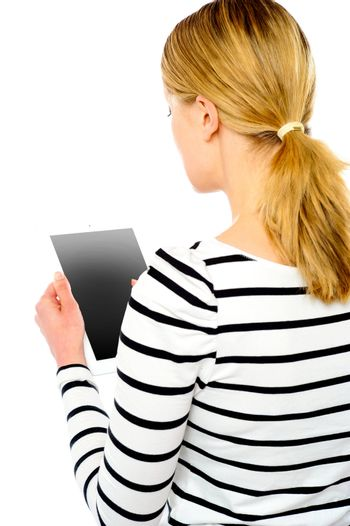 Rear view of teenage girl using touch screen device
