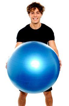 Man in sportswear holding big ball