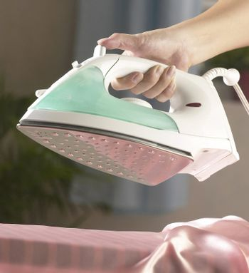 A person ironing some clothes.