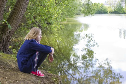 little girl sitting by the water