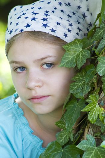 Portrait of young girl standing near tree at summer green park