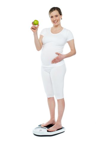 Pregnant woman standing on weighing machine