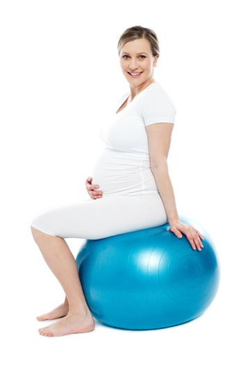 Pregnant lady sitting on exercise ball