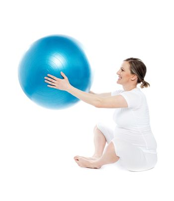 Pregnant woman sitting with exercise ball